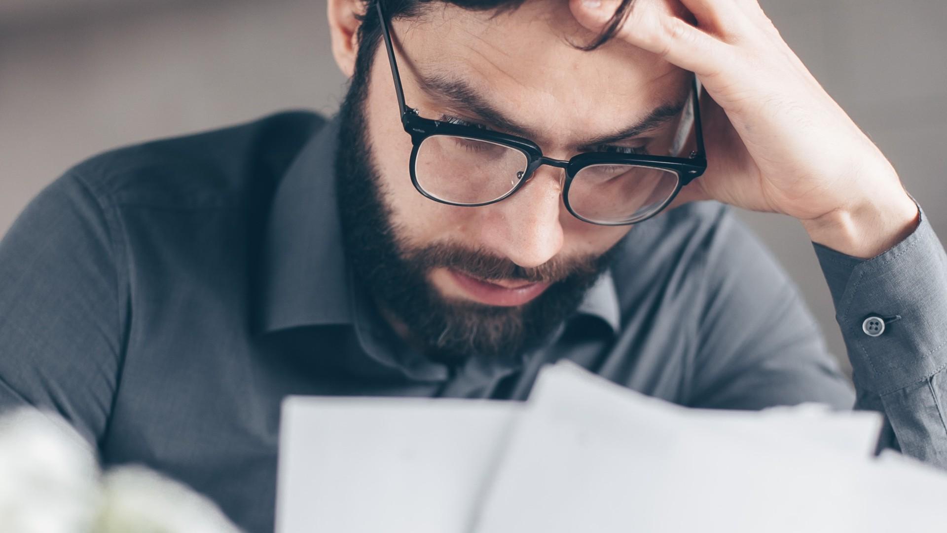 Mann blickt sorgenvoll auf Papiere