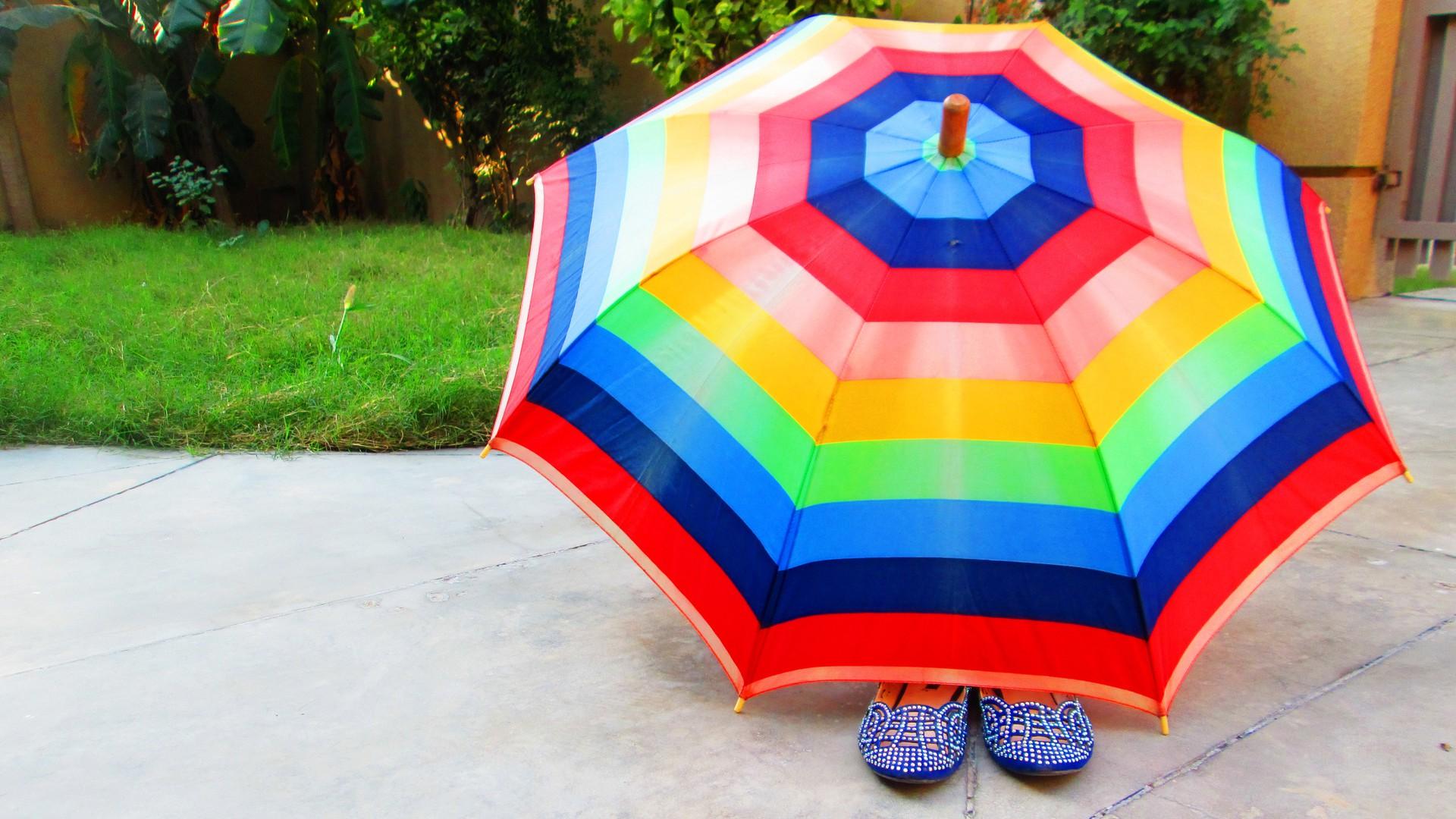 Person die unter einem Schirm versteckt ist