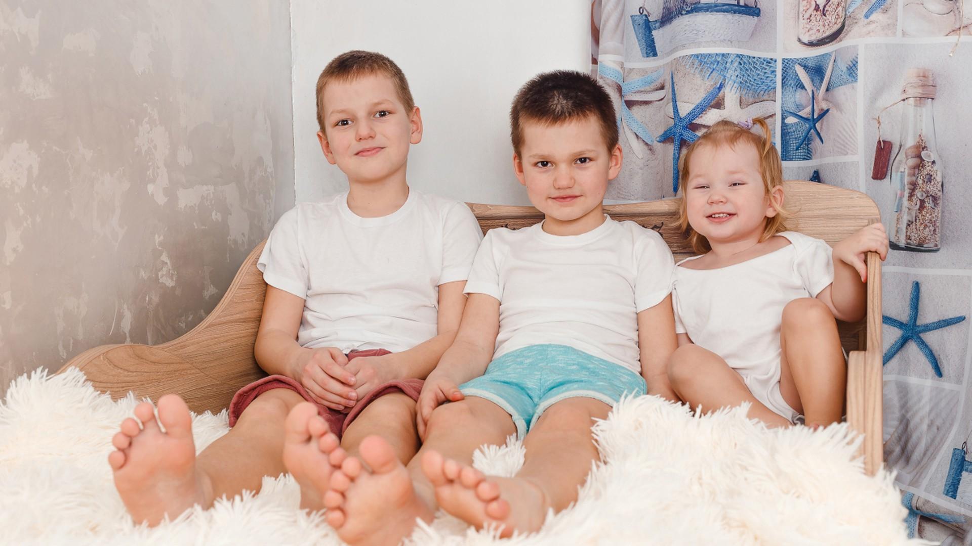 Drei Kinder sitzen nebeneinander in einem Bett