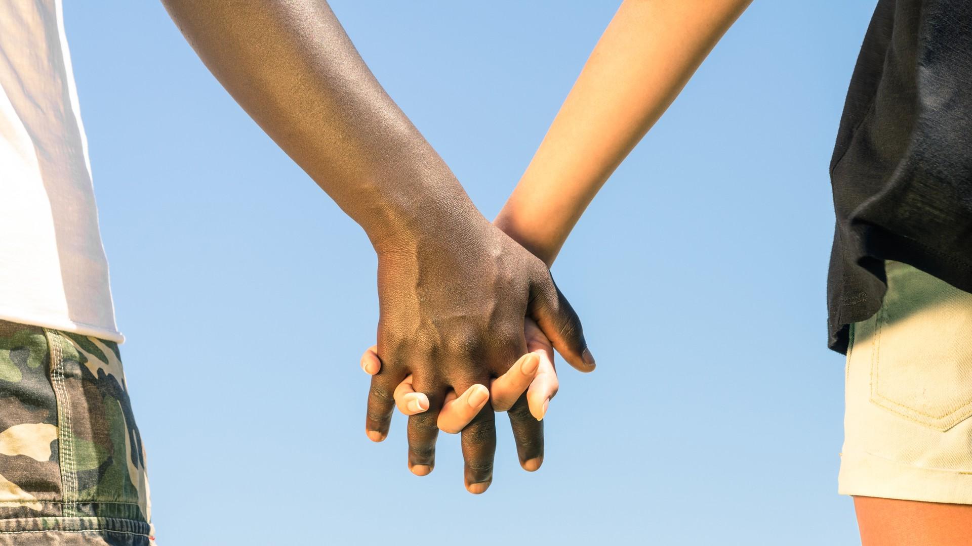 2 Menschen mit unterschiedlicher Hautfarbe Hand in Hand