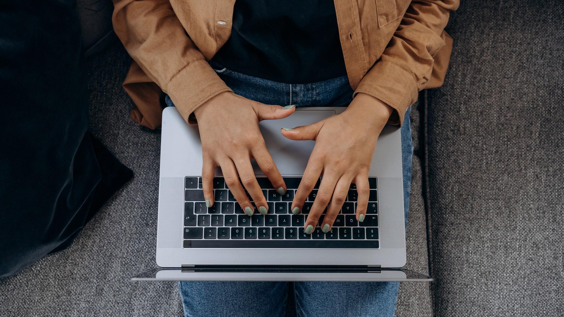 Hände tippen auf einer Laptop Tastatur
