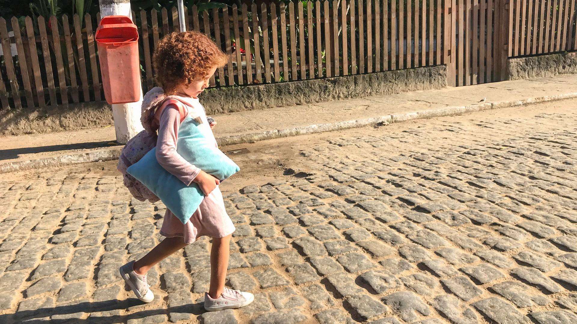 Kind auf der Straße unterwegs mit Polster